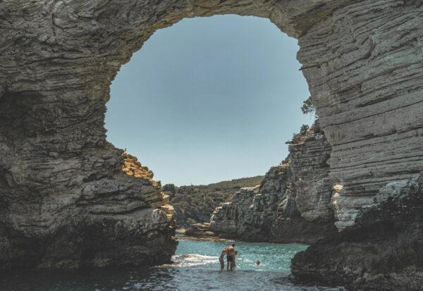Due persone sotto un arco di roccia